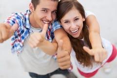 Tonårs- par med tum upp Arkivfoto