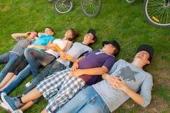 Tonårs- pojkar och flickor som ligger på gräset Fotografering för Bildbyråer