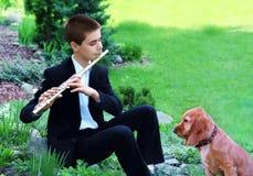 Tonårs- pojke med flöjten och hunden Arkivbilder