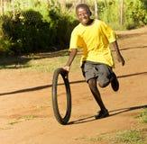 Tonårs- pojke som leker med däck - gul T-tröja Fotografering för Bildbyråer