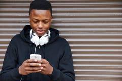 Tonårs- pojke som lyssnar till musik och använder telefonen i stads- inställning Arkivfoton