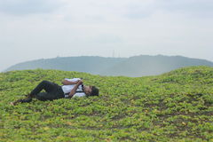 Tonårs- pojke som sover på gräs Royaltyfri Fotografi