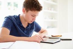 Tonårs- pojke som studerar genom att använda den Digital minnestavlan hemma Fotografering för Bildbyråer