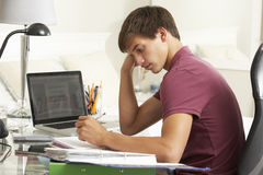 Tonårs- pojke som studerar på skrivbordet i sovrum Arkivbild