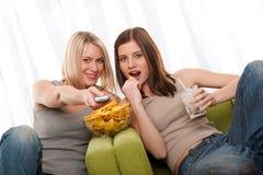 tonårs- tv två som för flickaseriedeltagare håller ögonen på Royaltyfri Fotografi