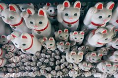 Tons of small dolls `the beckoning cat` known as maneki neko. At Gotokuji in Tokyo, JAPAN royalty free stock image