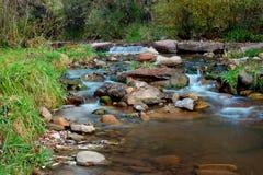 Tonto Creek Payson Arizona. Photo taken near end of fall season showing small waterfall, soft water movement, green foliage, some gold leaves, green plants Stock Photo