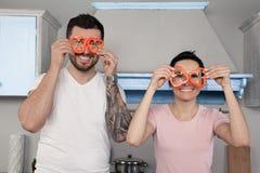 Tonto hermoso joven de los pares en la cocina Guardan pedazos de la pimienta búlgara alrededor de sus ojos y risa fotos de archivo