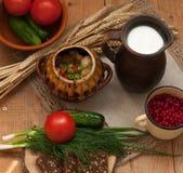 Tonwaren des gekochten Gemüses, des Topfes Milch, des hölzernen Brettes mit einer Tomate, der Gurken, des Brotes und der Grüns au Lizenzfreie Stockfotografie