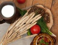 Tonwaren des gekochten Gemüses, des Topfes Milch, des hölzernen Brettes mit einer Tomate, der Gurken, des Brotes und der Grüns au Stockfotografie