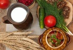 Tonwaren des gekochten Gemüses, des Topfes Milch, des hölzernen Brettes mit einer Tomate, der Gurken, des Brotes und der Grüns au Lizenzfreie Stockfotos