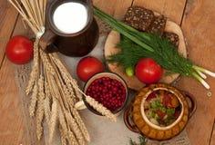 Tonwaren des gekochten Gemüses, des Topfes Milch, des hölzernen Brettes mit einer Tomate, der Gurken, des Brotes und der Grüns au Stockfoto