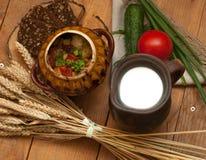 Tonwaren des gekochten Gemüses, des Topfes Milch, des hölzernen Brettes mit einer Tomate, der Gurken, des Brotes und der Grüns au Lizenzfreies Stockbild