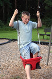 Too Big To Swing 2. Teenage boy trying to fit into a baby swing at a playground stock images