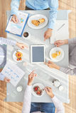 Too busy to eat. Business people watching presentation on tablet and having lunch Stock Photo