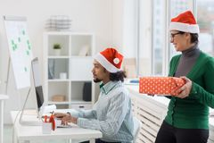 Too busy for xmas. Busy manager in Santa cap working in front of computer monitor while his colleague preparing him xmas surprise Royalty Free Stock Images
