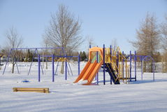 Too Cold For The Kids. The weather is too cold for the kids to come out to this playground despite the bright sunny day.  A park bench is buried in the snow in Stock Photos