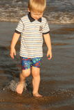 It is too cold to swim. Small boy walking on the irish beach in the sunset Royalty Free Stock Photography