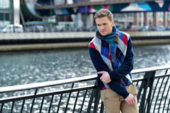 Too cold today in city. Young man leaning on metal railing at outdoors royalty free stock image