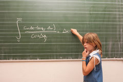 Too difficult math task for a small schoolgirl. Small schoolgirl trying to solve an integral equation in the school in front of the chalkboard Royalty Free Stock Images