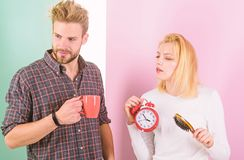 Too early awakening. Couple oversleep awakening hold alarm clock. Couple sleep not enough time. Family drink morning royalty free stock images