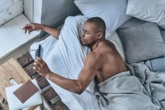 Too early. Top view of young African man turning off the alarm c Stock Image
