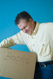 Too Heavy!!. A man grimacing as if with back pain from lifting a box filled with books Stock Image
