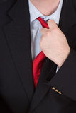 Too hot to handle. A business man loosening his red tie after getting hot under the collar Royalty Free Stock Photo