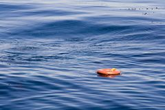 Too Late... Orange rescue ring floating over the deep blue ocean water with some small ripples on the left Royalty Free Stock Photos