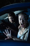 Too late to call for help. Shot of a young women screaming and a men sitting behind her in a car Royalty Free Stock Image