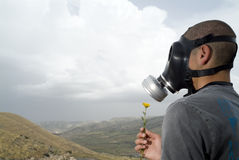 Too late for a wish. Man with a gas mask holding a dandilion Royalty Free Stock Photos