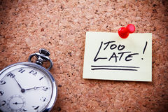 Too late!. Written on a post note and hanged on the cork-board with an old pocket watch Royalty Free Stock Photography