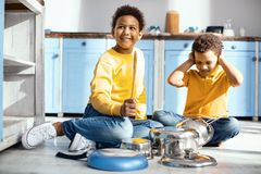 Upbeat little boys creating loud noises by drumming on saucepans. Too loud. Cheerful little boys sitting on the kitchen floor and creating loud noises by Stock Photo