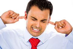 This is too loud!. Closeup portrait of man holding fingers inside ears to block out noise, isolated on white background royalty free stock image