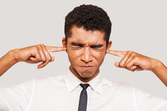 This is too loud!. Frustrated young Afro-American man in formalwear plugging ears with his fingers and keeping eyes closed while standing against grey background Royalty Free Stock Images