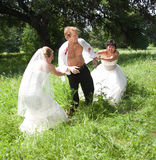 Too many brides. Two women in wedding gowns play tug o' war with a bare chested groom Royalty Free Stock Photos