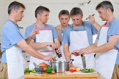 Too many cooks. Composite of five cloned men trying to cook together but too many cooks have spoiled the broth Stock Images