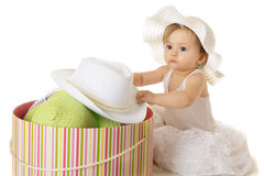 Too Many Hats!. An adorable baby girl looking spacey in her petticoat as she digs into a large, colorful, filled hat box.  On a white background Royalty Free Stock Photo