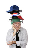 Too Many Hats. A discouraged businessman or academic wearing too many hats. Isolated on white royalty free stock photo
