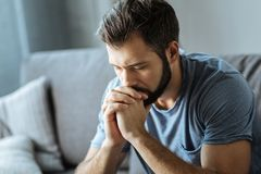 Unhappy young man holding his chin Stock Images