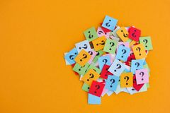 Too Many Questions. Pile of colorful paper notes with question marks on yellow background. Closeup stock photography