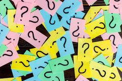 Too Many Questions on wooden background. Pile of colorful paper notes with question marks. top view.  Royalty Free Stock Photo