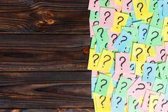 Too Many Questions on wooden background. Pile of colorful paper notes with question marks. top view copy space.  Stock Photos