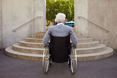 Too many steps for wheelchair user. Elderly woman in wheelchair looking at stairs Stock Images
