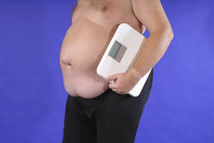 Too much. Fat man with bathroom scale Stock Photos