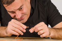 Too much dificult. Guy having a hard time with needle and thread Stock Photo