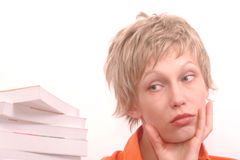 Too much information. Worried woman with lot of books to be read royalty free stock image