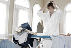 Too much ironing to do. Woman throws hands on head with frustration over how much ironing she has left to finish Royalty Free Stock Photos