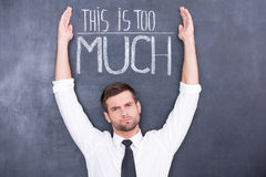 This is too much for me. Confused young man standing against chalkboard with raised hands Royalty Free Stock Images