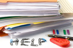 Too Much Paperwork. Stacks of paperwork and file folders with correction tape, signature arrows, a pen, and paperclips spelling HELP Royalty Free Stock Image